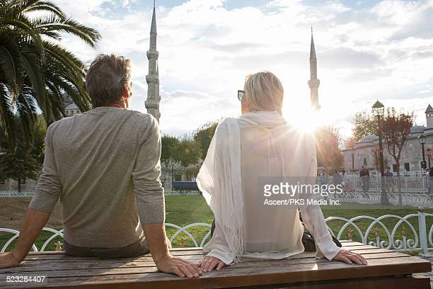 Couple watch sunrise over Blue Mosque, gardens