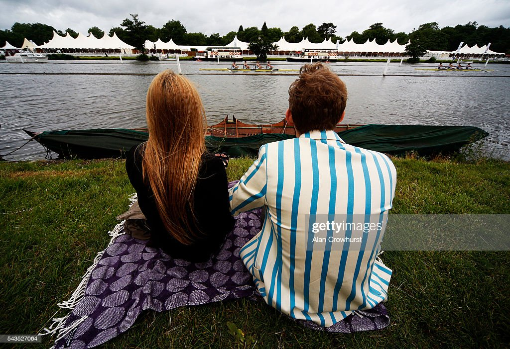 A couple watch the racing from the river bank during the Henley Royal Regatta on June 29, 2016 in Henley-on-Thames, England.