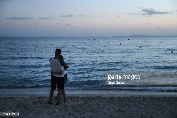 A couple watch the sunset at the beach on the Ballermann stretch on July 25 2017 in Palma de Mallorca Spain The term Ballermann which combines the...