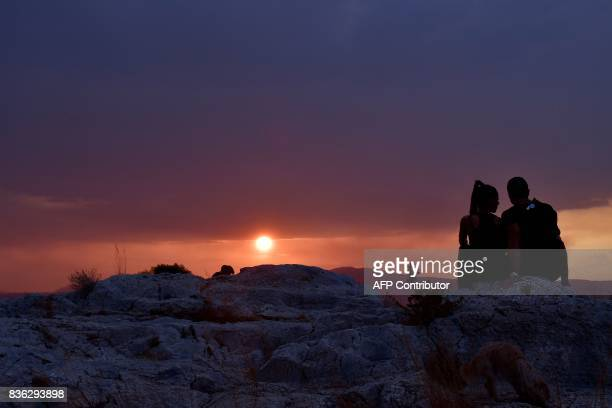 A couple watches a sunset on Filipappou hill in Athens as heavy rain cloud hang over the city on August 21 2017 / AFP PHOTO / LOUISA GOULIAMAKI