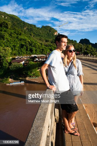 A couple watches the sunset from a bridge. : Stock Photo