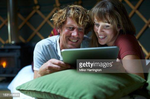 Couple watching film on iPad inside yurt, : Stock Photo