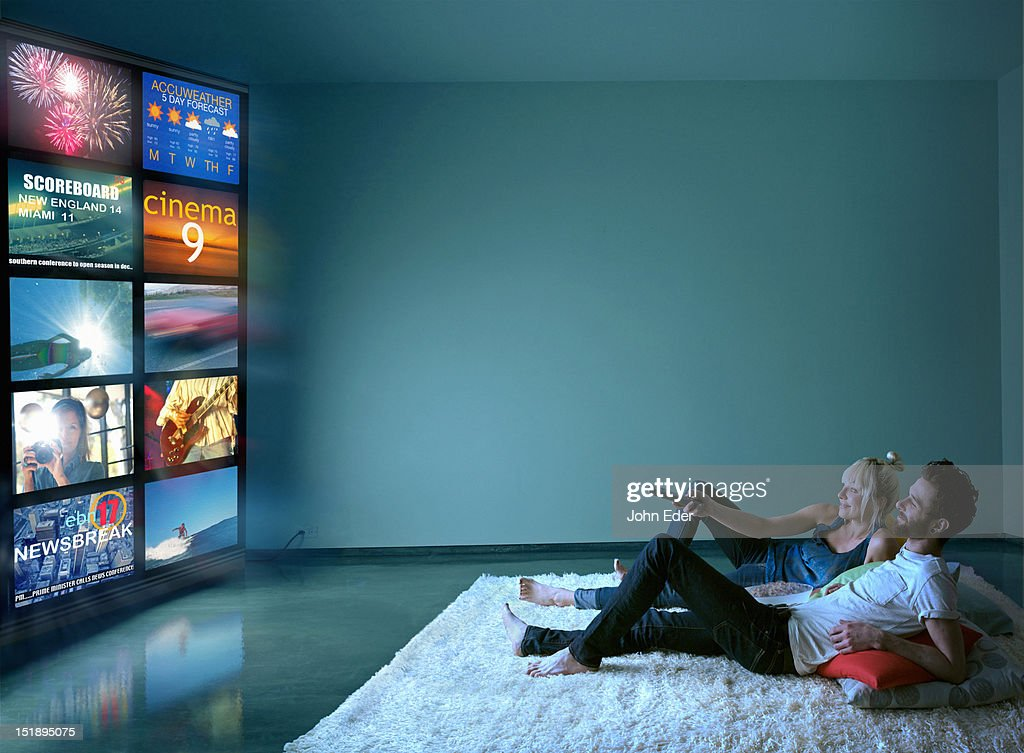 Couple Watching Multiple TV Screens : Stock Photo