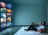 Couple Watching Multiple TV Screens