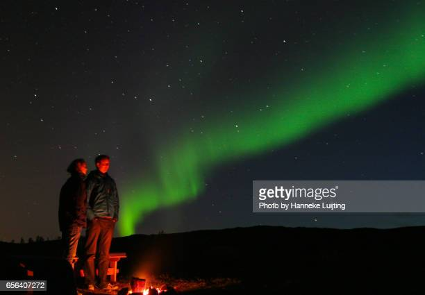 Couple watching Northern Lights by a campfire