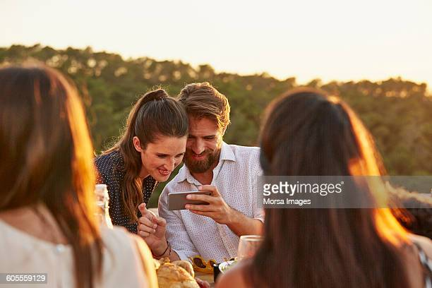 Couple watching photographs on smart phone