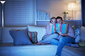 Couple watching scary movie on sofa