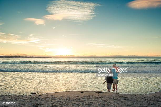 A couple watching sunset at Monterey beach California USA