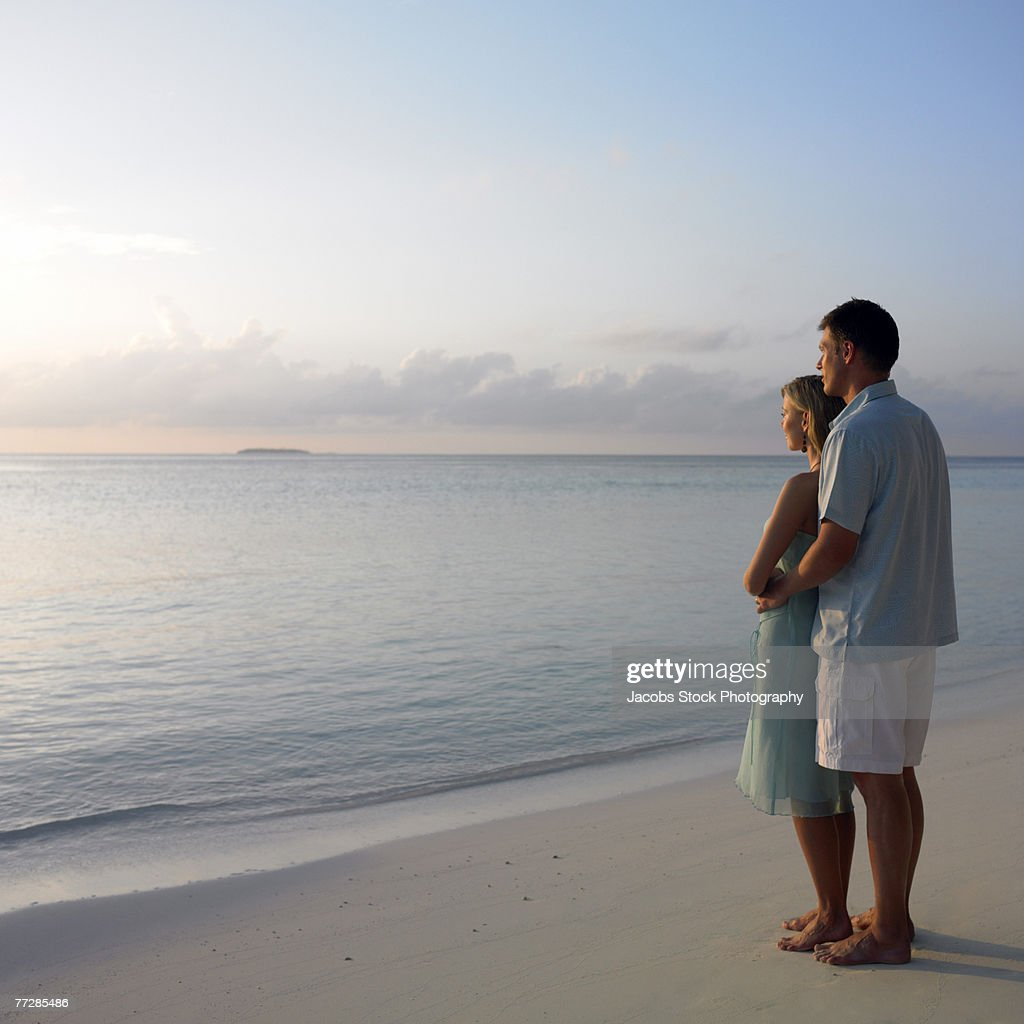 Couple watching sunset from beach