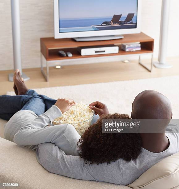 A couple watching television and eating popcorn