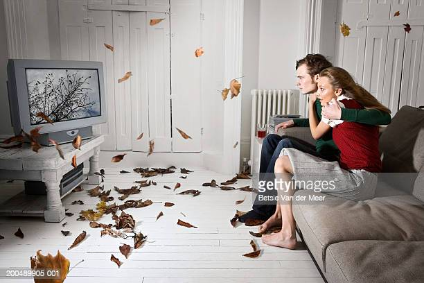 Couple watching television as storm blows from screen into living room