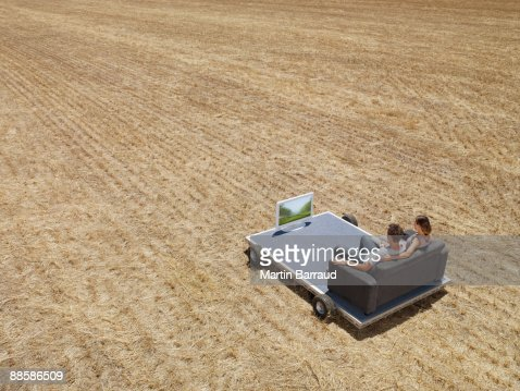 Couple watching television in field : Stock Photo