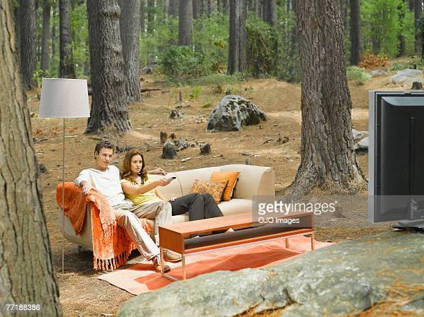 Ein Paar vor dem Fernseher im Freien im Wald