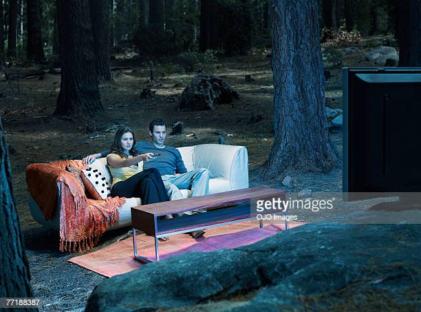 A couple watching television outdoors in the woods