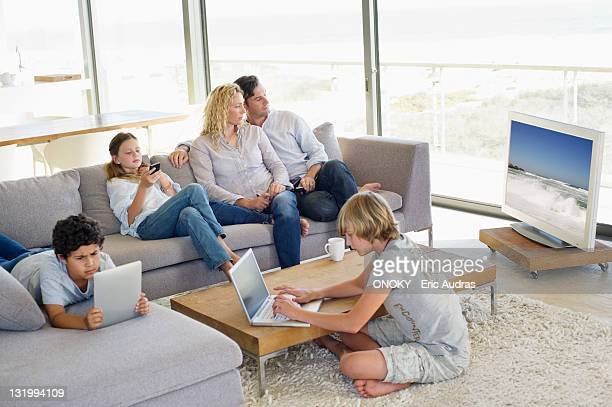 Couple watching television set while kids busy using electronic gadgets