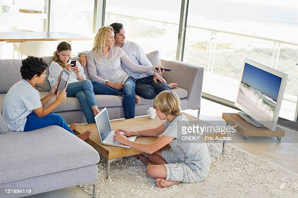 Couple watching television set while their children busy in different activities