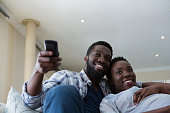 Couple watching television together in living room at home