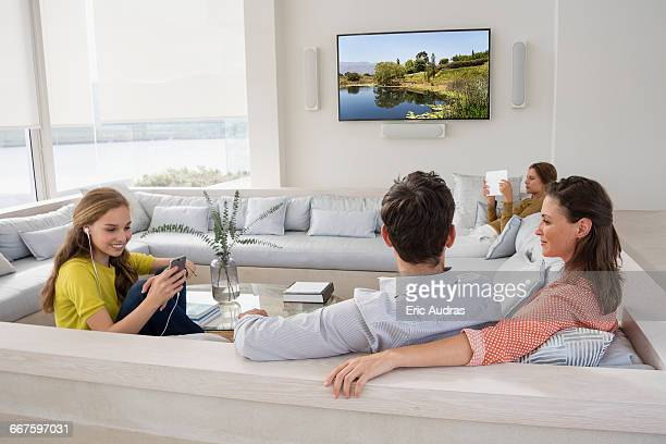Couple watching television with their children busy in different activities