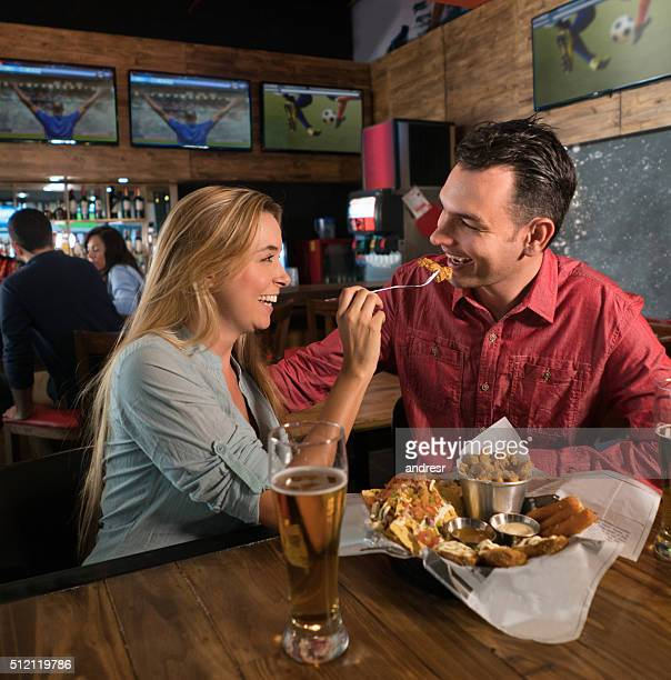 Couple watching the game at a sports bar and eating