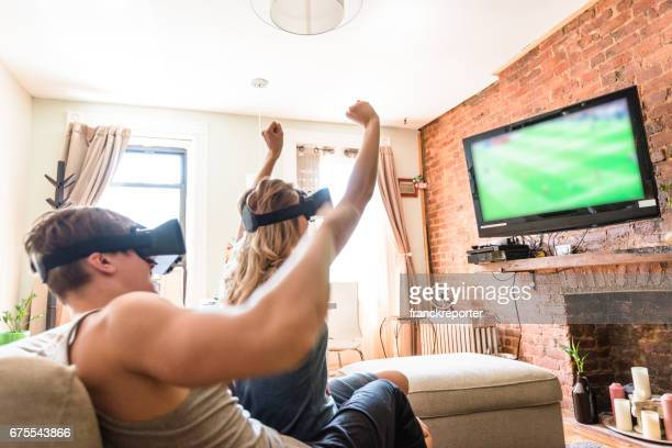 couple watching the match on tv with vr headset