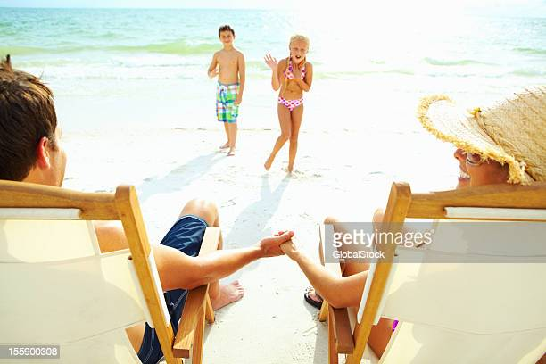 Couple watching their children play