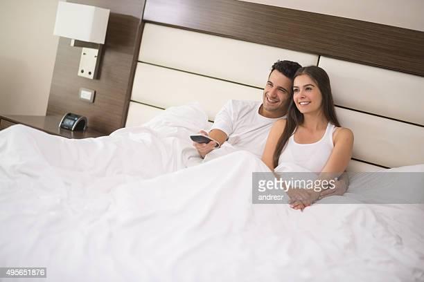 Pareja en la cama viendo televisión