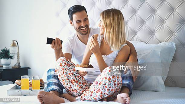 Couple watching tv in bedroom.