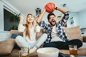 Couple watching basketball game in living room while eating popcorn and drinking beer