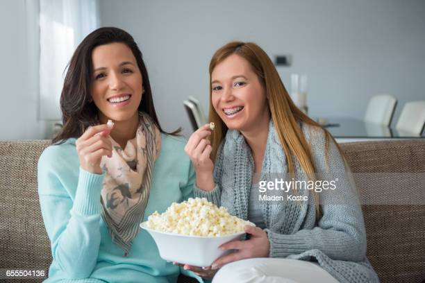 Couple watching TV on a sofa and eating popcorn