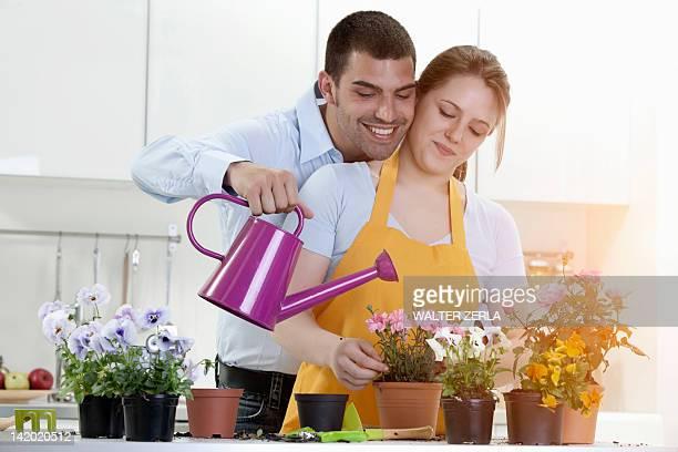 Paar gießen Topfpflanzen im Innenbereich