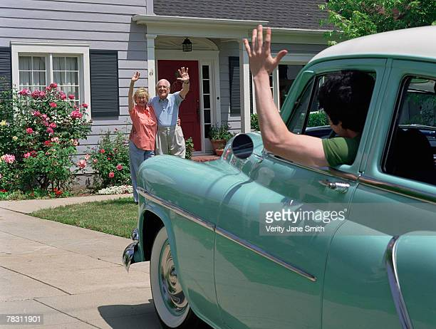 Couple waving to man in car