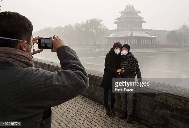 A couple wear protective masks as they have their picture taken outside the Forbidden City on a day of heavy pollution on November 30 2015 in Beijing...