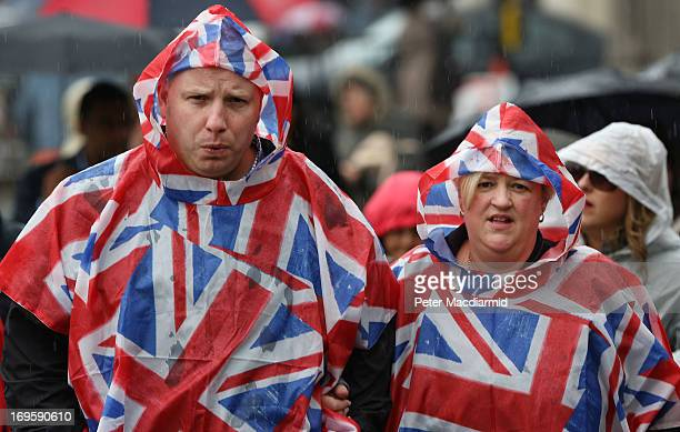 A couple wear Union flag decorated waterproofs during a rainstorm near Parliament on May 28 2013 in London England Heavy rain is falling in London...
