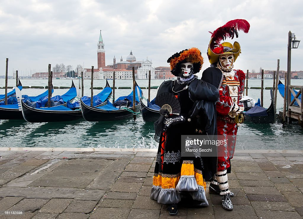 A couple wearing a Carnival Costumes pose in Saint Mark's Square on February 9, 2013 in Venice, Italy. The 2013 Carnival of Venice runs from January 26 - February 12 and includes a program of gala dinners, parades, dances, masked balls and music events.
