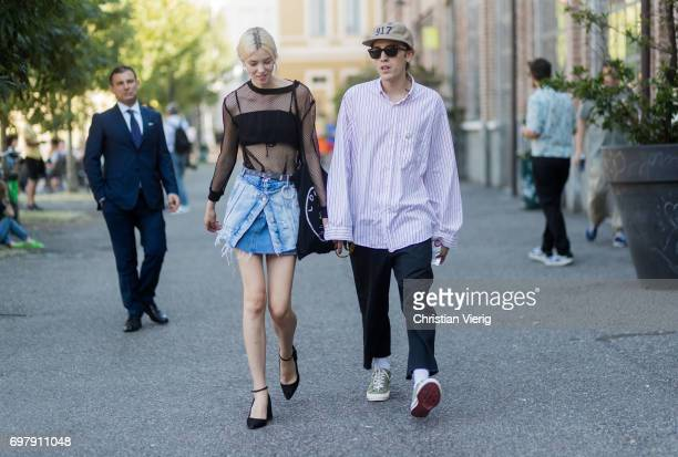 A couple wearing a sheer top denim skirt and button shirt cap is seen outside Malibu 1992 during Milan Men's Fashion Week Spring/Summer 2018 on June...