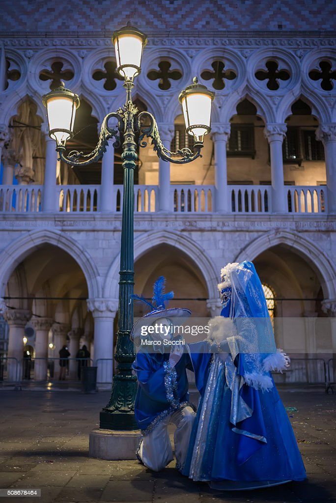 A couple wearing carnival costumes pose in front of the Doge Palace on February 06, 2016 in Venice, Italy. The 2016 Carnival of Venice will run from January 23 to February 9 and includes a program of gala dinners, parades, dances, masked balls and music events.