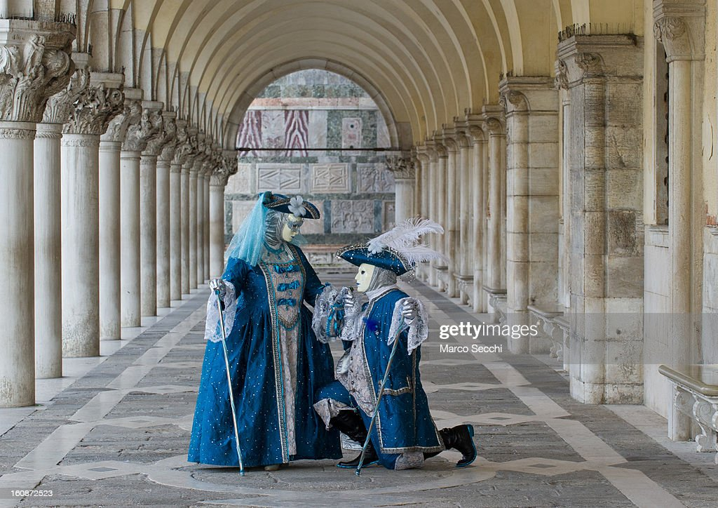 A couple wearing Carnival Costumes poses in Saint Mark's Square underneath the Doge Palace on February 7, 2013 in Venice, Italy. The 2013 Carnival of Venice runs from January 26 - February 12 and includes a program of gala dinners, parades, dances, masked balls and music events.
