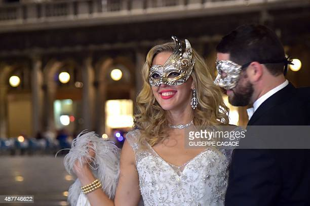 A couple wearing carnival masks is pictured Piazza San Marco during the 72nd Venice International Film Festival on September 11 2015 in Venice AFP...