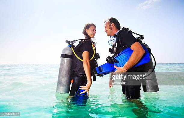 Couple wearing diving equipment in the water.