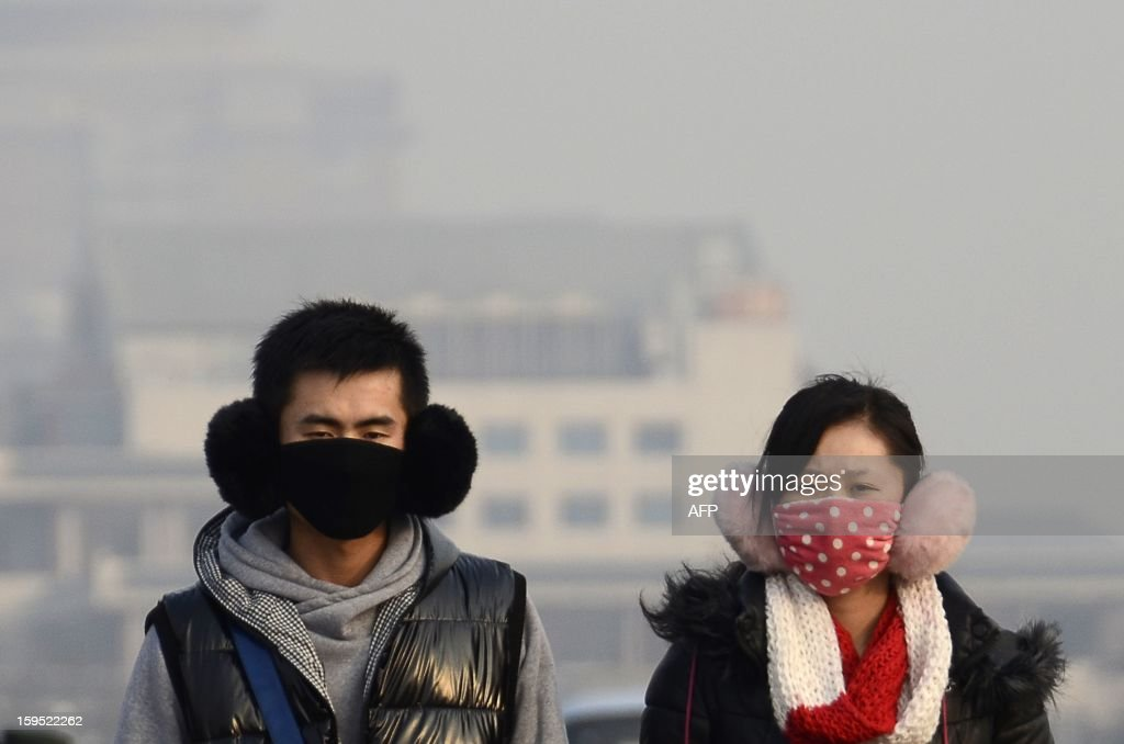 A couple wearing face masks look on as they make their way along a street in Beijing on January 15, 2013.Shares in a Chinese face mask manufacturer soared on January 15, as investors looked for opportunities to cash in on the severe air pollution that has blanketed large swathes of China. AFP PHOTO / WANG ZHAO