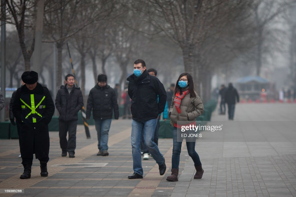 A couple wearing face masks walks in a busy shopping area during polluted weather in Beijing on January 13, 2013. Dense smog shrouded Beijing, with pollution at hazardous levels for a second day and residents advised to stay indoors, state media said. AFP PHOTO / Ed Jones
