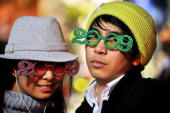 A couple wearing glasses with year '2009' design arrive to join thousands of others to welcome the New Year at Universal City in California on...
