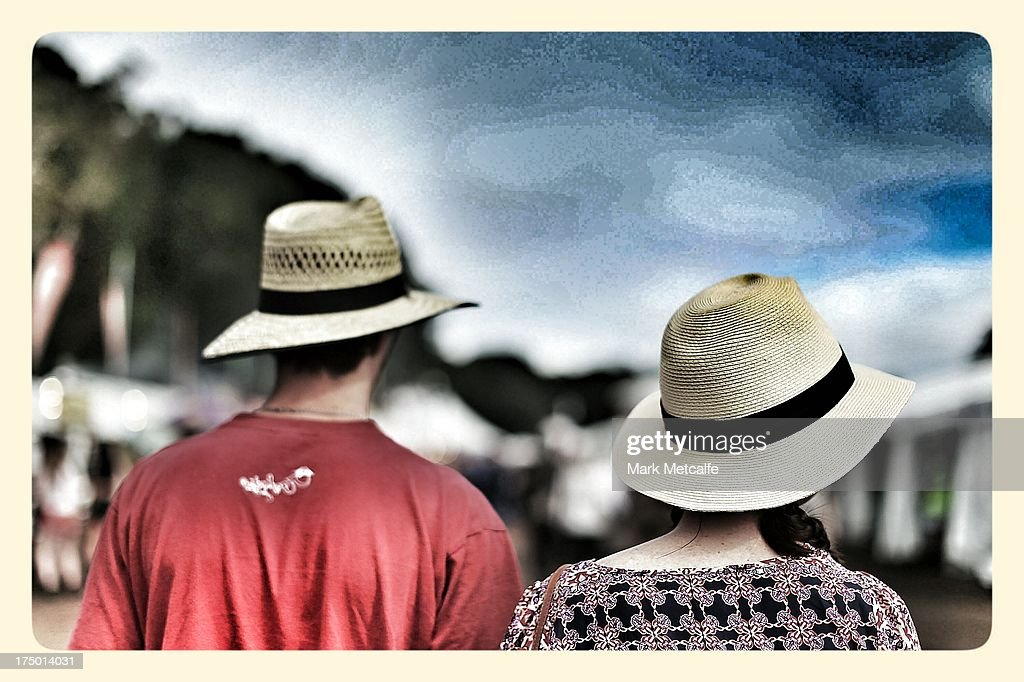 A couple wearing hats walk through the festival site on day 3 of the 2013 Splendour In The Grass Festival on July 28, 2013 in Byron Bay, Australia.