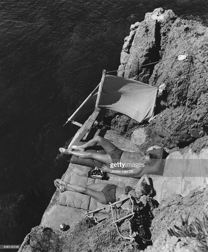 Couple wearing identical swimwear sunbathing on rocks at Cap Roux, Cote d'Azur (French Riviera) - 1939 - Photographer: Regine Relang - Published by: 'Die Dame' 12/1939 Vintage property of ullstein bild