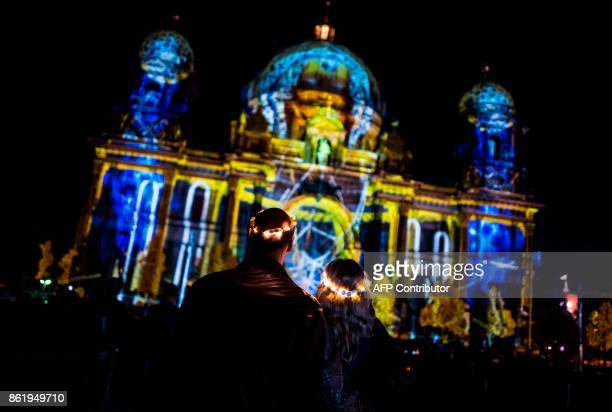A couple wearing light crowns watch a light projection on the facade of the Berlin Cathedral on the last day of the yearly Festival of Lights in...