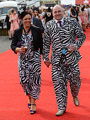 Couple wearing matching outfits enjoy the atmosphere on Day 2 of the Aintree races at Aintree Racecourse on April 10 2015 in Liverpool England