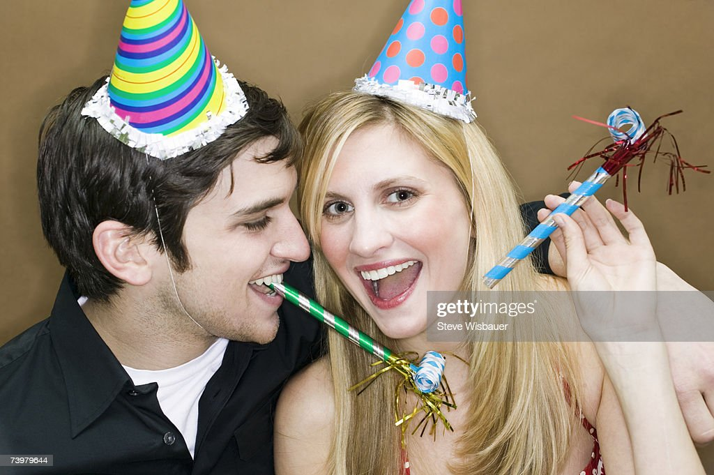 Couple wearing party hats, holding party horn blowers, laughing : Stock Photo