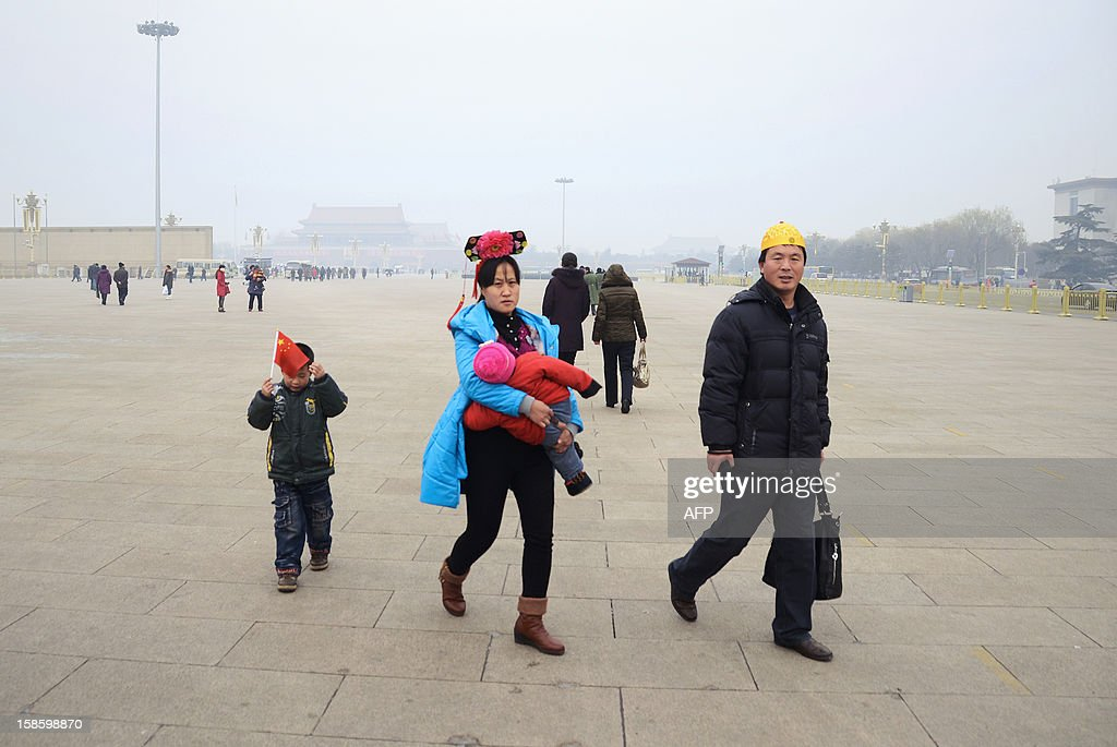 A couple wearing Qing dynasty style headwear walk with their children in Tiananmen square in Beijing on December 20, 2012. China said on December 18 it faces a bleak foreign trade environment in 2013 due to ongoing global economic weakness, as the Asian export powerhouse appears set to miss this year's trade growth target.