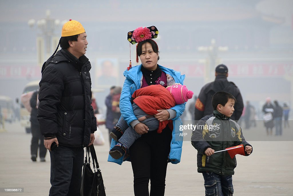 A couple wearing Qing dynasty style headwear walk with their children in Tiananmen square in Beijing on December 20, 2012. China said on December 18 it faces a bleak foreign trade environment in 2013 due to ongoing global economic weakness, as the Asian export powerhouse appears set to miss this year's trade growth target. AFP PHOTO / WANG ZHAO