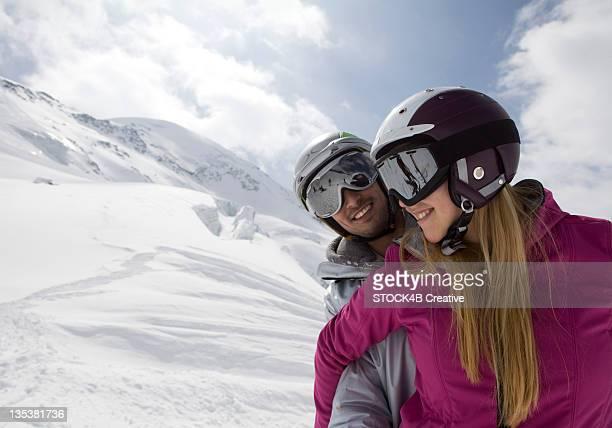 Couple wearing ski suits in alpine winter landscape